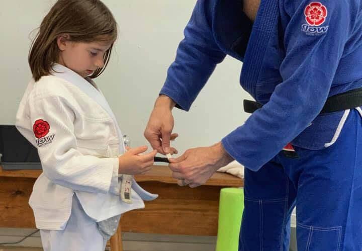 little girl getting a stripe on her jiu jitsu belt at Select Jiu Jitsu
