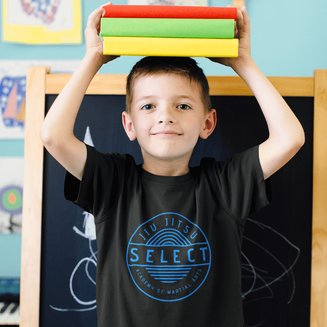 young boy wearing a select jiu jitsu black tee and holding school books